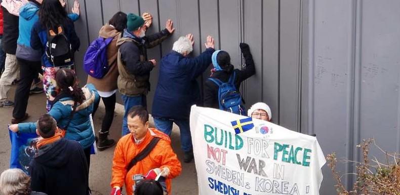 Agneta Norberg håller upp sin banderoll: Bygg för fred inte för krig, vid aktionen på Jejuön